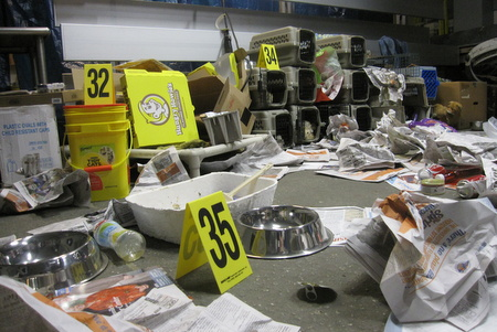 The mock crime scenes included piles of trash, litterboxes, animal carriers, medical records, stuffed animals to represent victims, and a wide variety of debris commonly found at animal hoarding scenes.