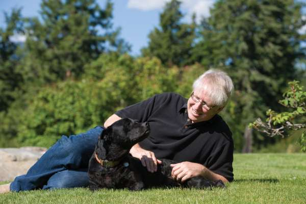 Dr. Marty becker layong in grasss with black dog