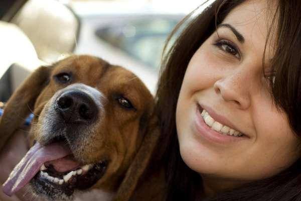 Woman with brown hair smiling next to dog with tongue hanging out of mouth
