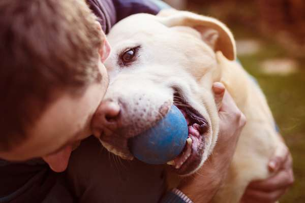 Happy man and dog with ball