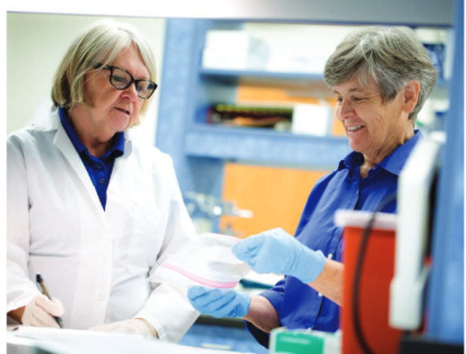 Sylvia Tucker, a biological scientist at the college, looks on as Dr. Cynda Crawford inspects samples that had recently tested positive for H3N2 dog flu.