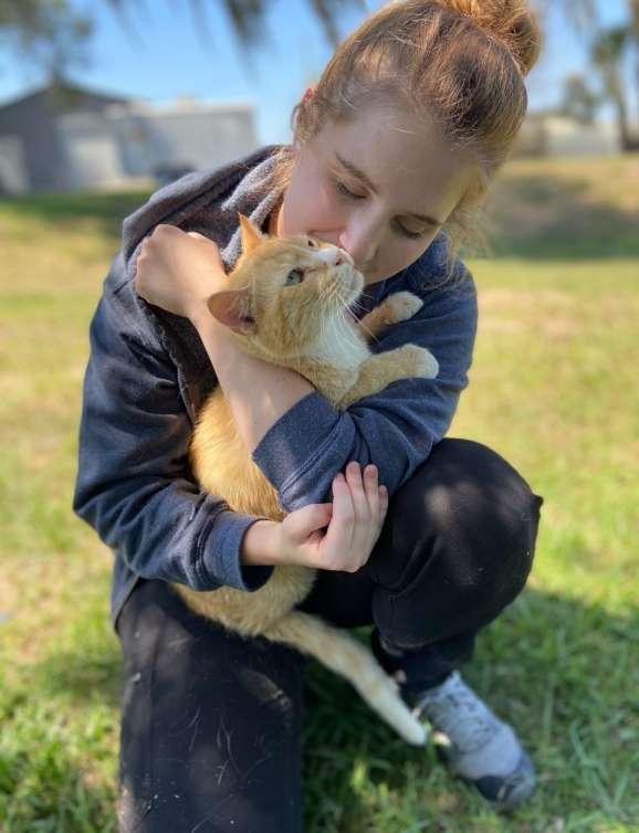 Dr. Amelia Sikora cuddling an orange cat